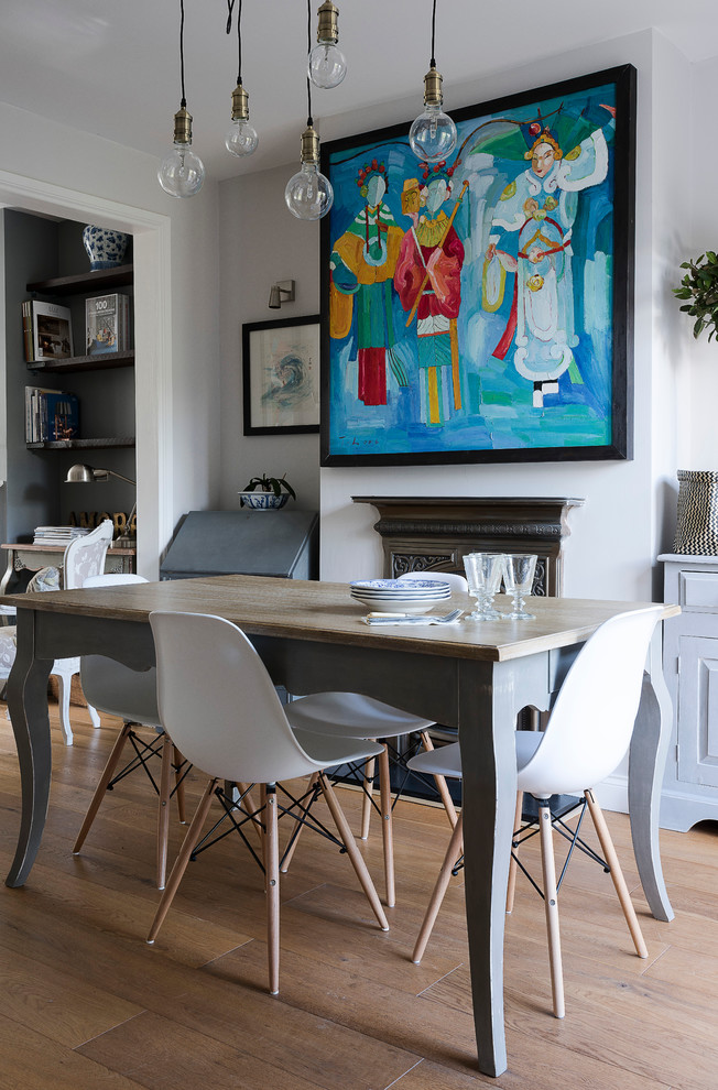 Example of a transitional light wood floor dining room design in London with white walls and a standard fireplace