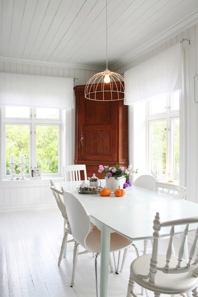 Inspiration for a scandinavian painted wood floor and white floor dining room remodel in Other with white walls