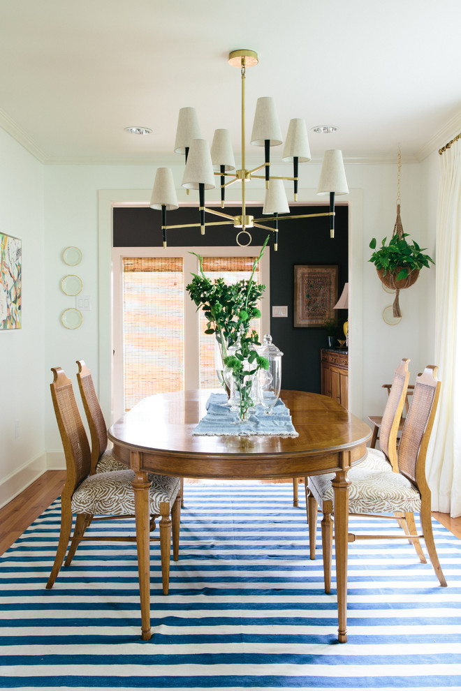 Inspiration for a mid-sized eclectic medium tone wood floor enclosed dining room remodel in New Orleans with white walls