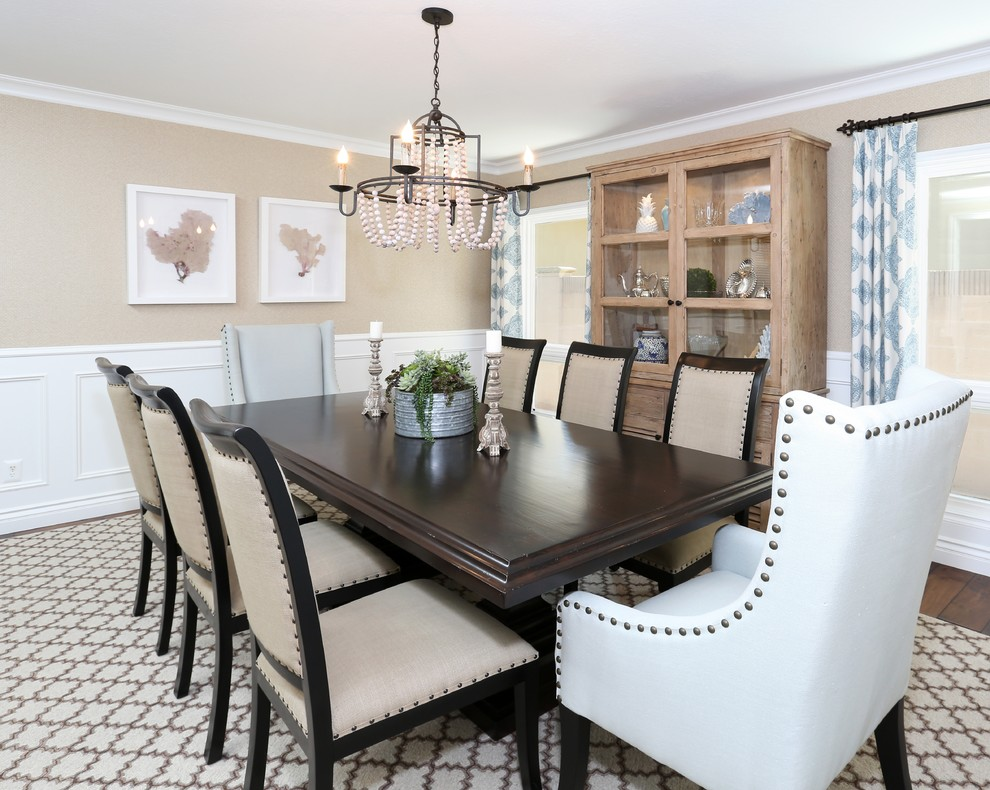 Example of a beach style medium tone wood floor enclosed dining room design in Orange County with beige walls