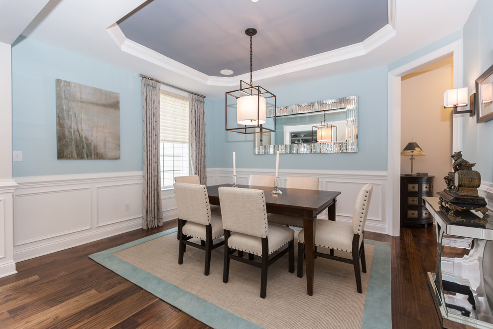 Example of a large classic medium tone wood floor and brown floor enclosed dining room design in Philadelphia with blue walls and no fireplace
