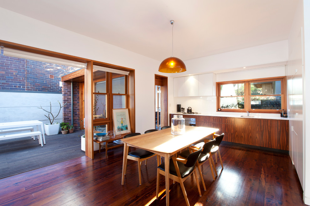 Trendy dark wood floor kitchen/dining room combo photo in Sydney with white walls