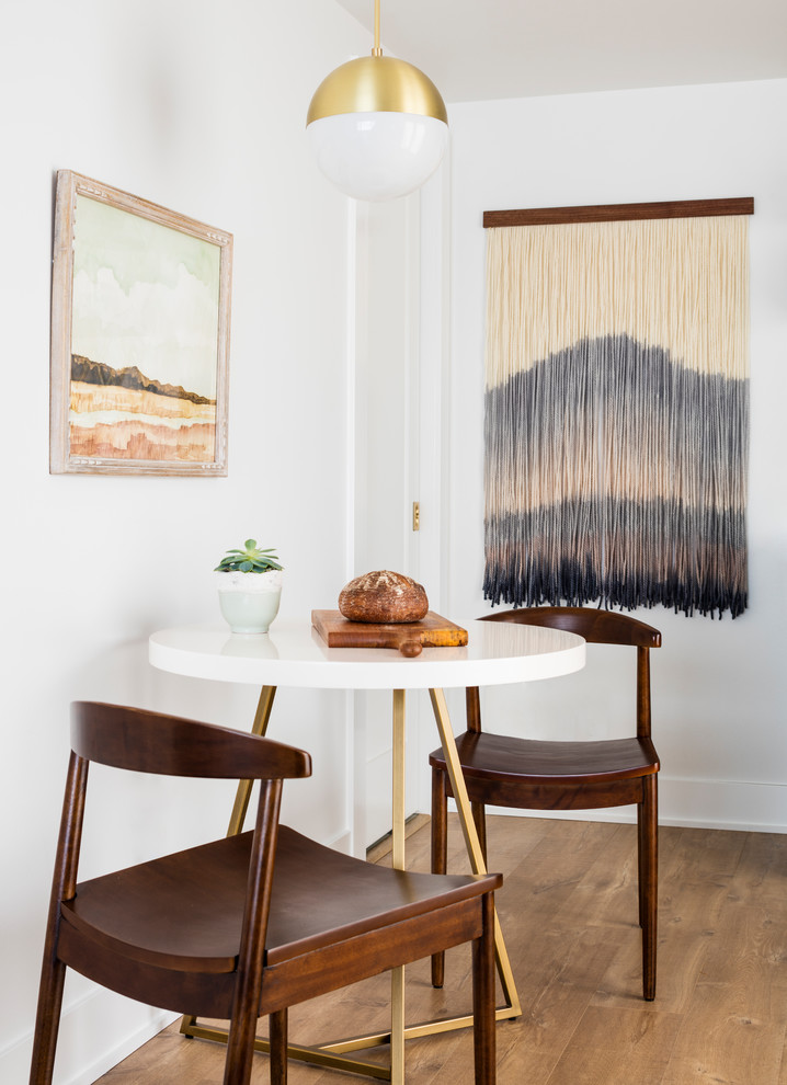 Example of a small danish laminate floor and brown floor kitchen/dining room combo design in Seattle with white walls and no fireplace