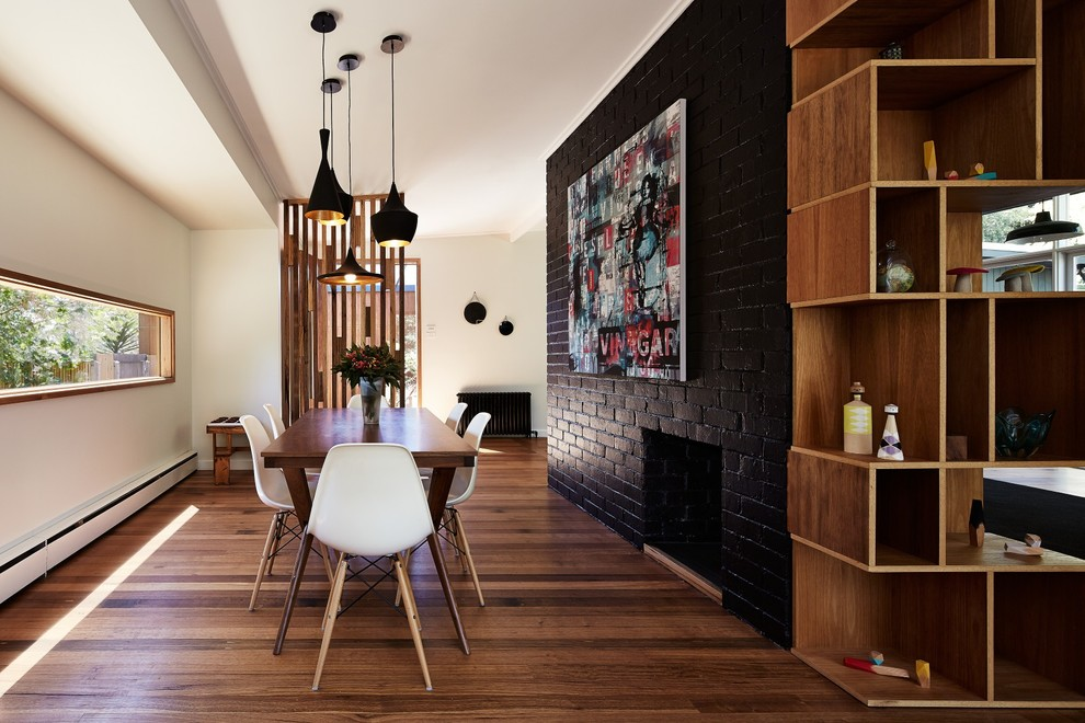 Example of a mid-sized trendy medium tone wood floor dining room design in Melbourne with black walls, a standard fireplace and a brick fireplace