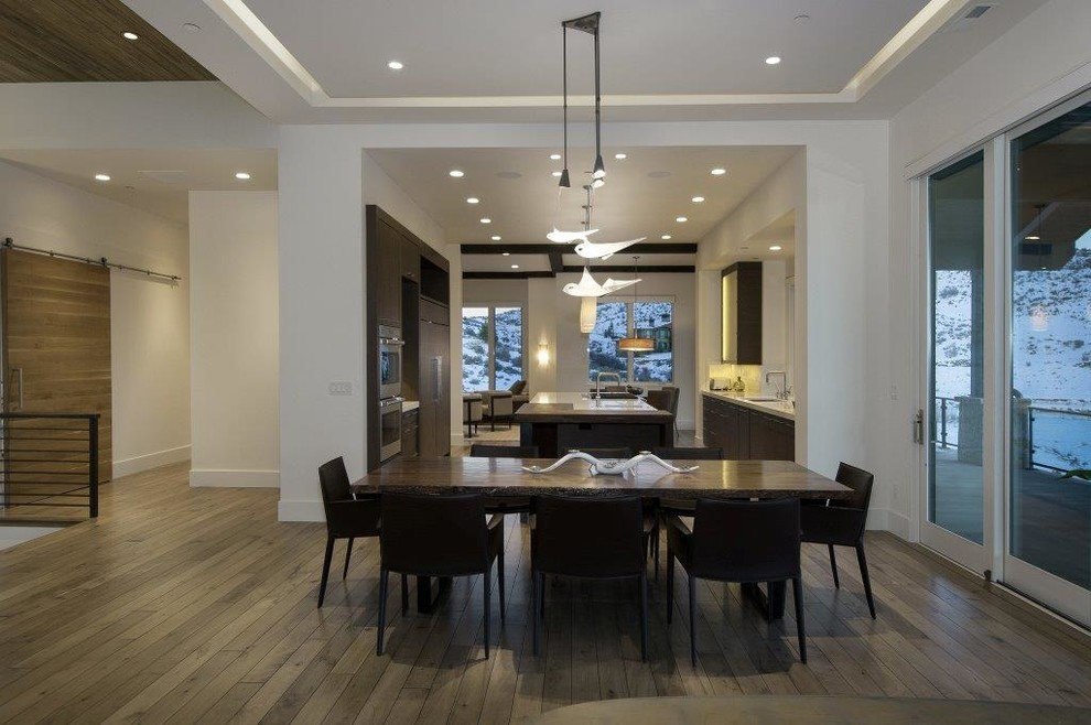 Mid-sized trendy medium tone wood floor great room photo in Salt Lake City with white walls and no fireplace