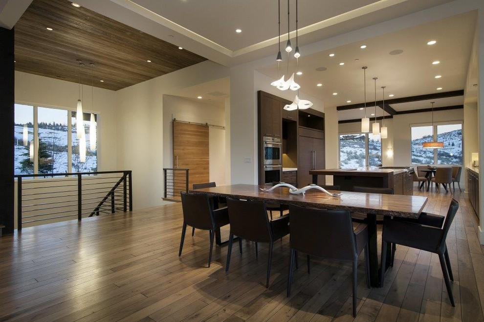 Example of a mid-sized trendy medium tone wood floor great room design in Salt Lake City with white walls and no fireplace