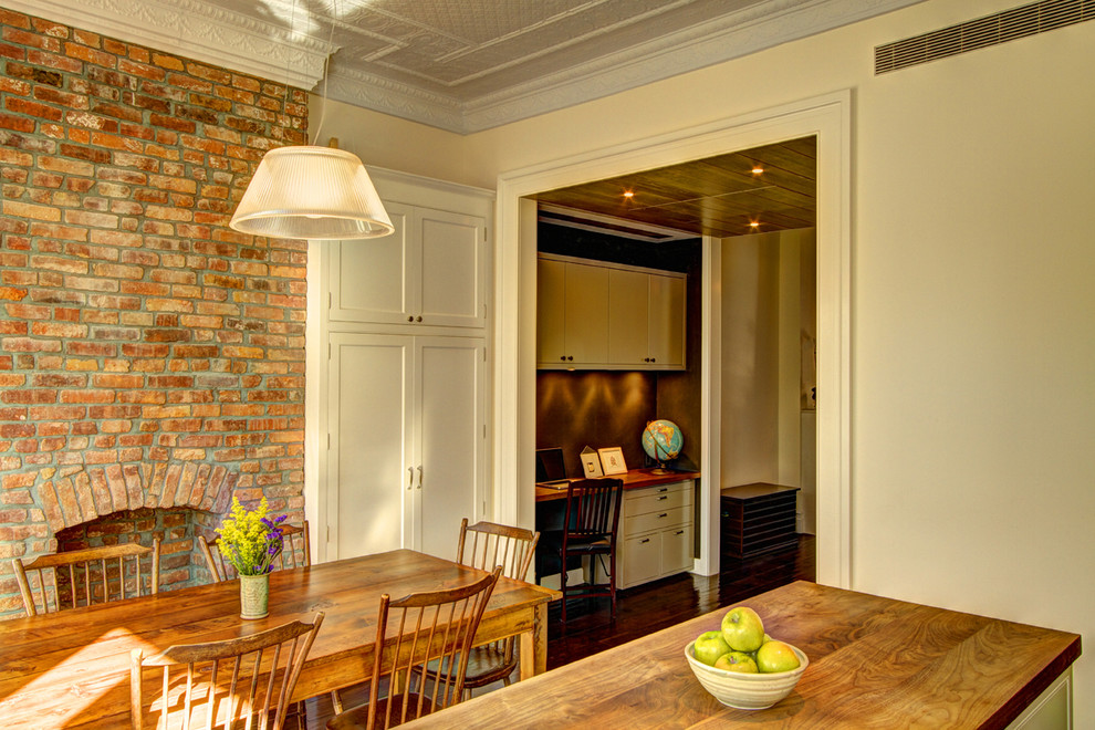 Example of a classic dining room design in New York with beige walls and a brick fireplace
