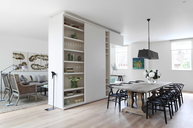 Photo of a contemporary open plan dining room in London with white walls and light hardwood flooring.