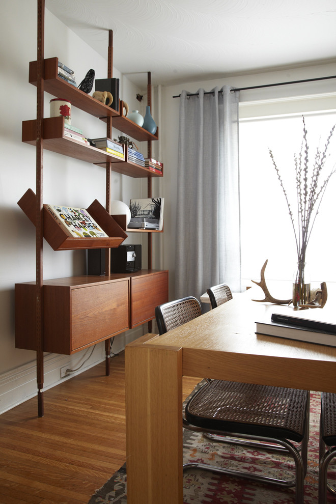 Example of a danish medium tone wood floor dining room design in Toronto with white walls