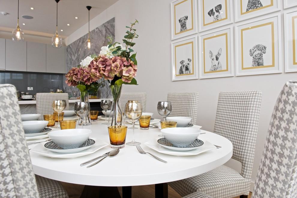 Ispirazione per una sala da pranzo aperta verso la cucina classica con pareti grigie e parquet chiaro