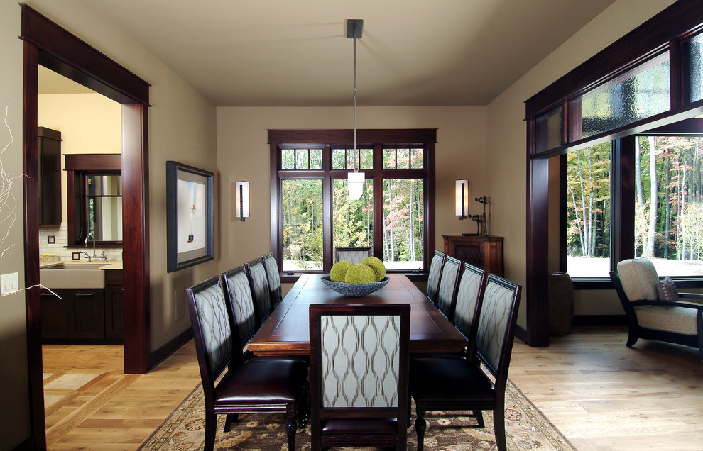 Elegant medium tone wood floor dining room photo in Grand Rapids with beige walls
