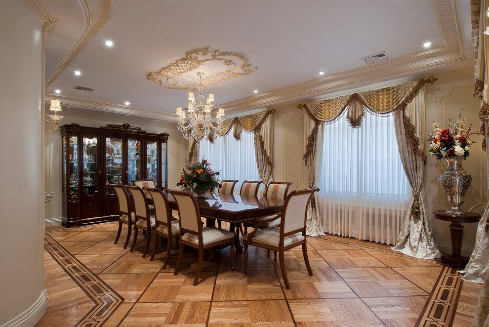 Example of a large classic medium tone wood floor dining room design in New York with beige walls