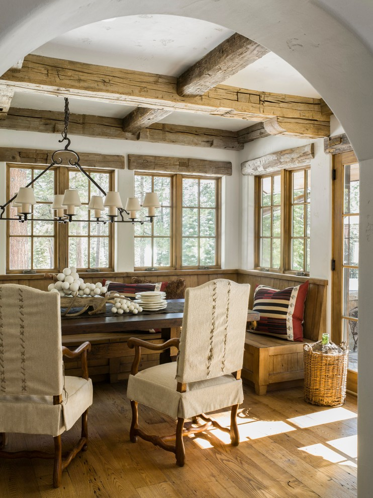 Example of a mountain style medium tone wood floor kitchen/dining room combo design in San Francisco with white walls
