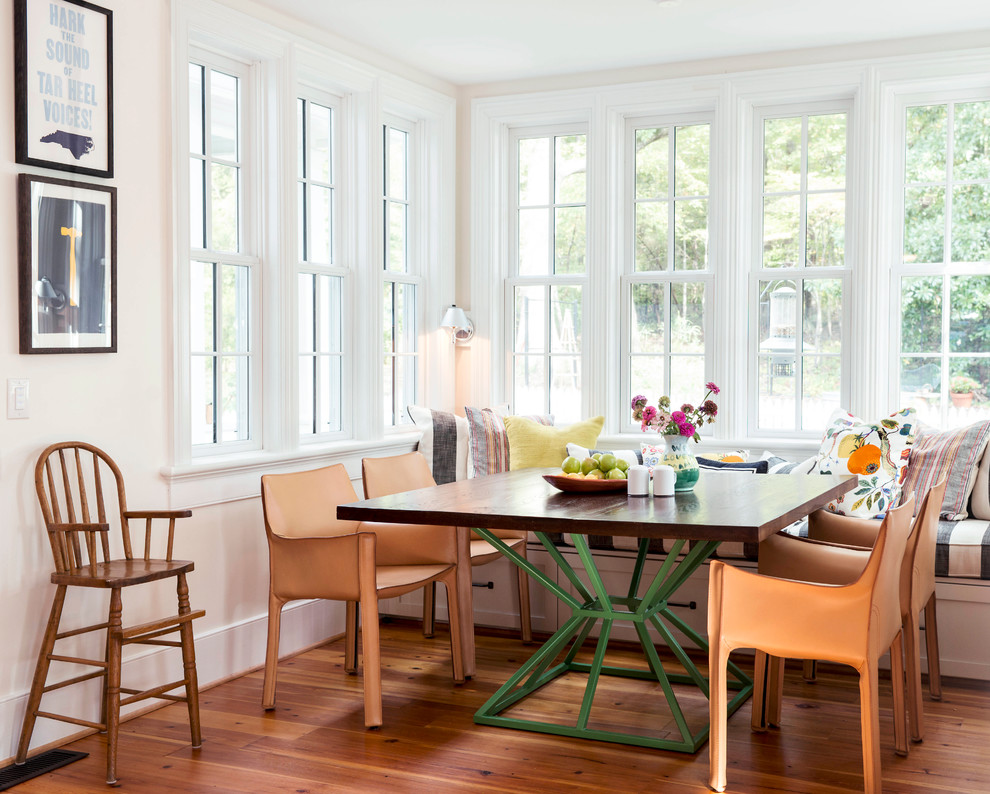 Example of a country medium tone wood floor dining room design in Raleigh with beige walls