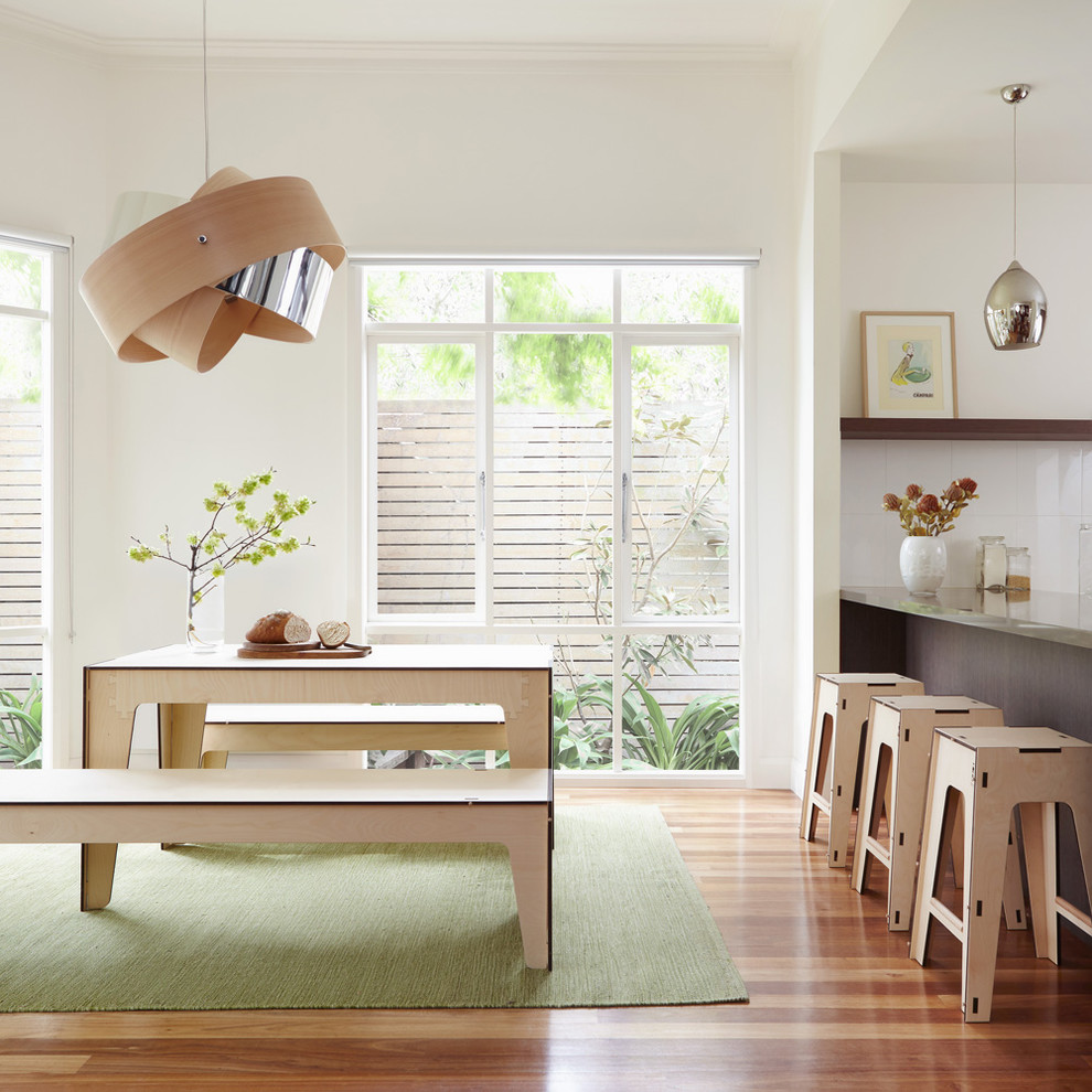 Example of a mid-sized trendy medium tone wood floor kitchen/dining room combo design in Melbourne with white walls