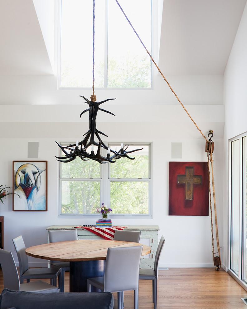 Minimalist medium tone wood floor dining room photo in Kansas City with white walls