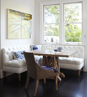 A kitchen corner with a white banquette for its nook