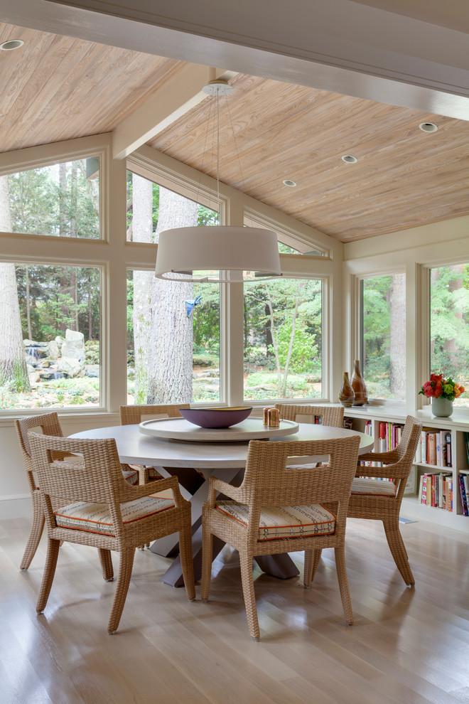 Cette photo montre une salle à manger chic de taille moyenne avec un mur beige, un sol en bois clair et un sol beige.