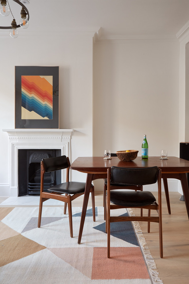 Mid-sized danish light wood floor dining room photo in London with white walls, a wood stove and a plaster fireplace