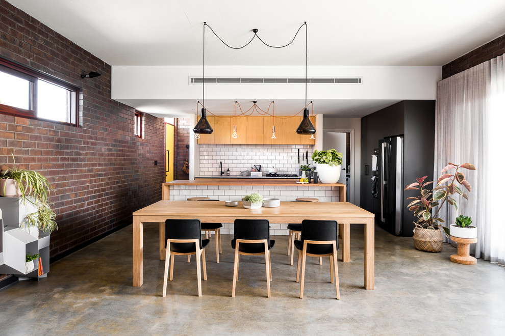 Inspiration for a mid-sized industrial concrete floor and gray floor kitchen/dining room combo remodel in Perth with multicolored walls