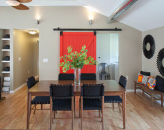 Red barn door with full view of dining table. modern dining room