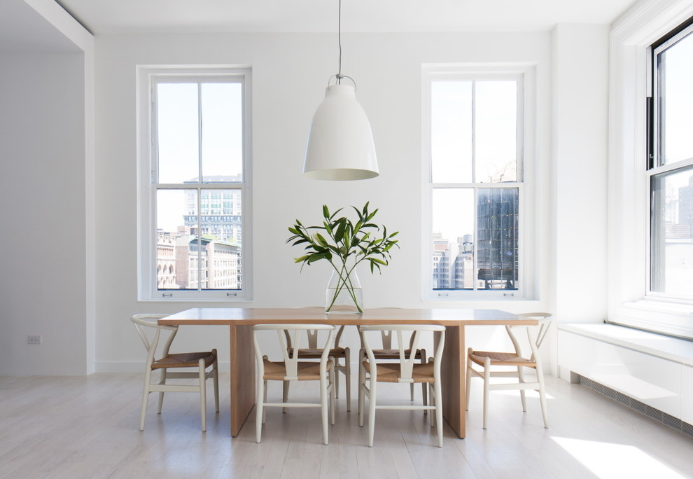 Example of a danish light wood floor and white floor dining room design in New York with white walls