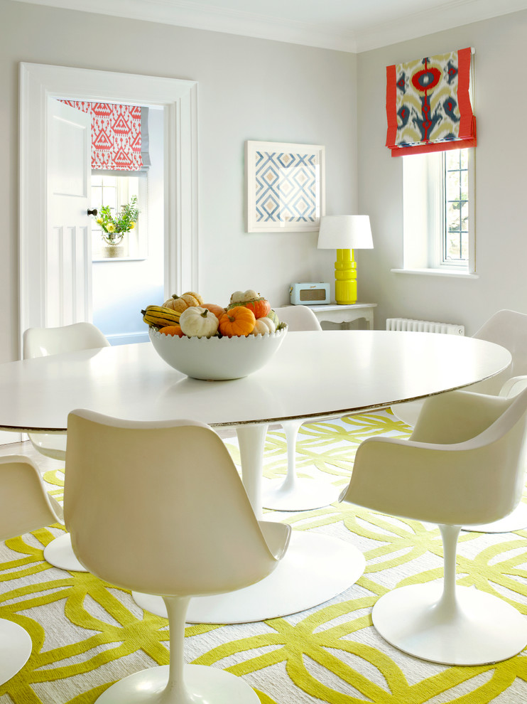 Example of a trendy carpeted and yellow floor dining room design in London with gray walls
