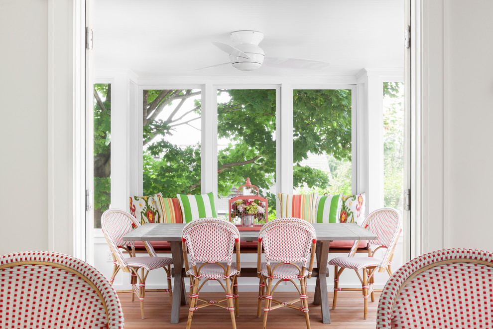 Enclosed dining room - coastal medium tone wood floor enclosed dining room idea in New York with white walls