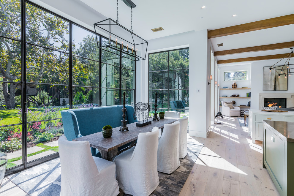 Example of a transitional light wood floor dining room design in Los Angeles with white walls