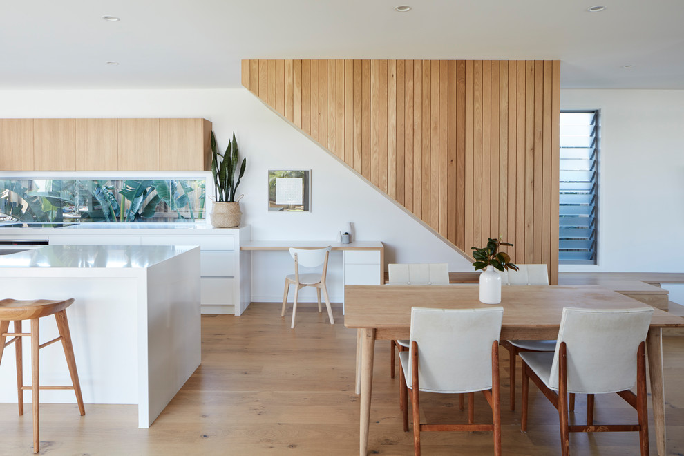 Example of a trendy light wood floor and beige floor kitchen/dining room combo design in Brisbane with white walls