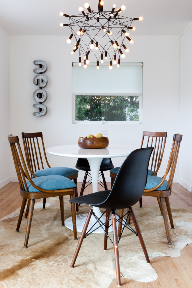 Example of an eclectic medium tone wood floor dining room design in Los Angeles with white walls