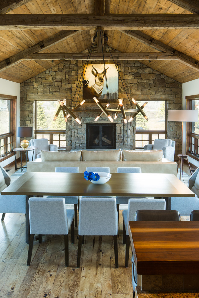 Great room - rustic medium tone wood floor great room idea in Other with white walls, a standard fireplace and a stone fireplace