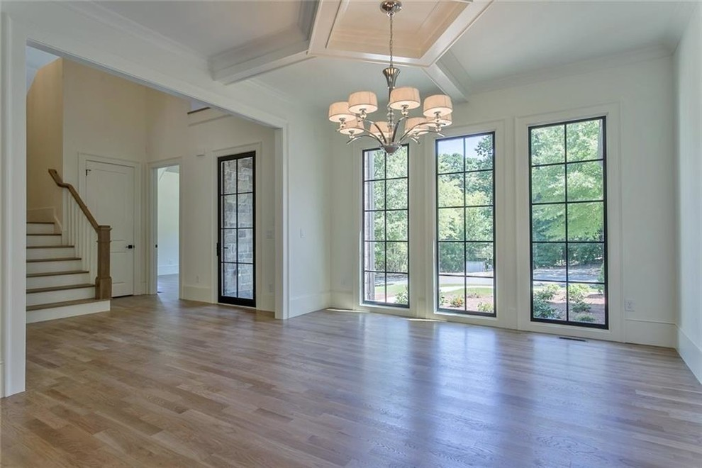Large transitional light wood floor and gray floor enclosed dining room photo in Atlanta with white walls