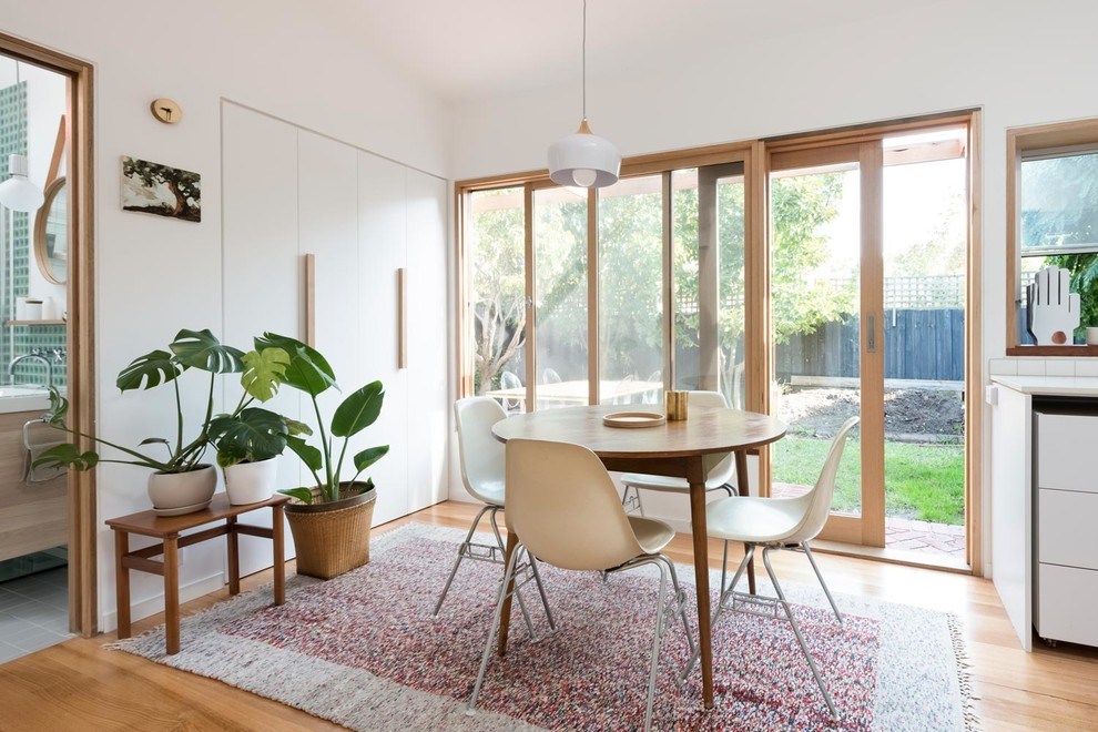 This is an example of a small scandi kitchen/dining room in Melbourne with white walls, light hardwood flooring and brown floors.