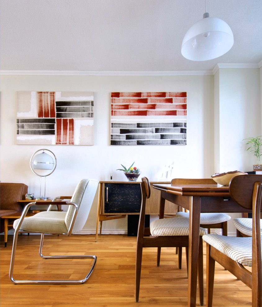 Inspiration for a 1960s medium tone wood floor dining room remodel in Toronto with white walls