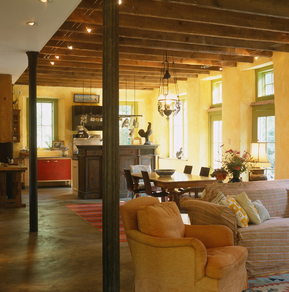 Inspiration for a mid-sized country concrete floor and brown floor great room remodel in Baltimore with yellow walls and no fireplace