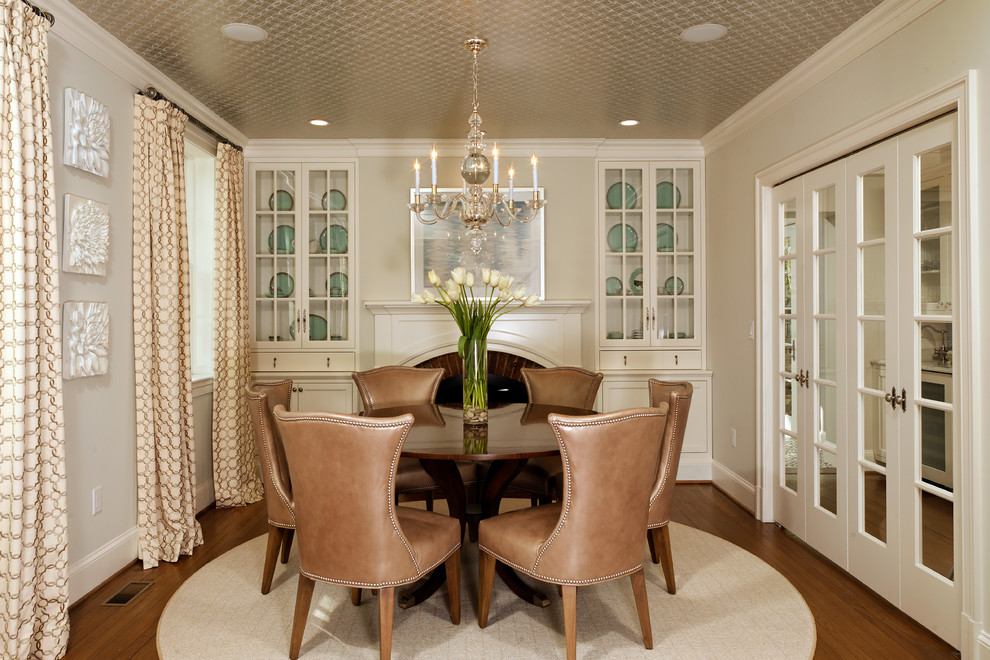 Elegant dark wood floor enclosed dining room photo in DC Metro with a standard fireplace and beige walls