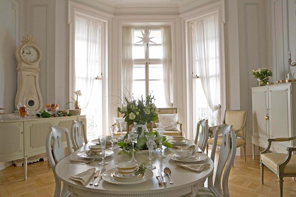 Example of a classic medium tone wood floor dining room design in Other with white walls