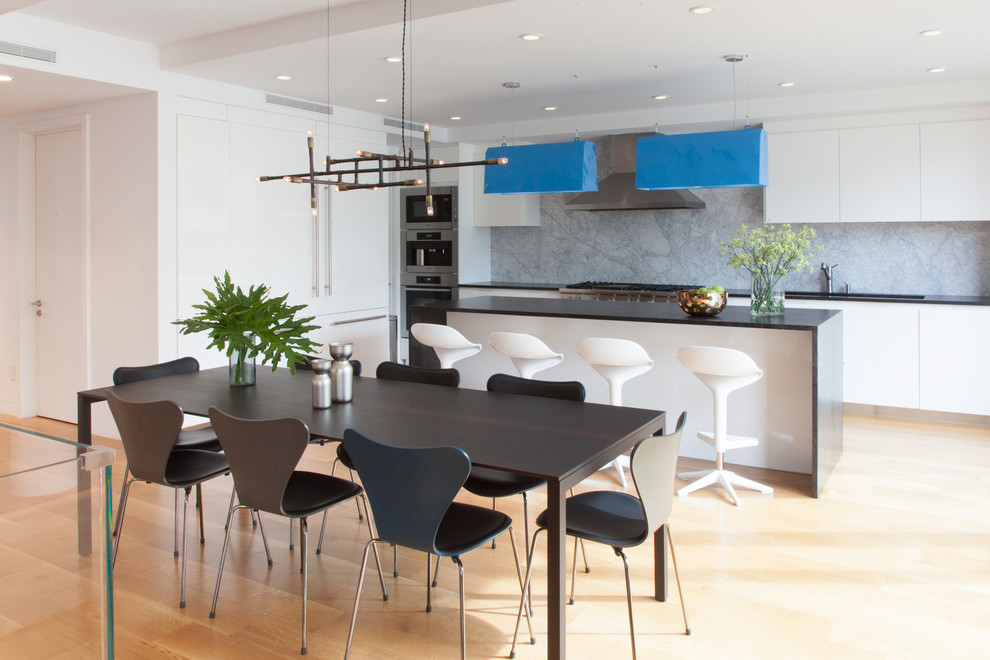 Example of a mid-sized minimalist light wood floor and brown floor kitchen/dining room combo design in New York with white walls and no fireplace