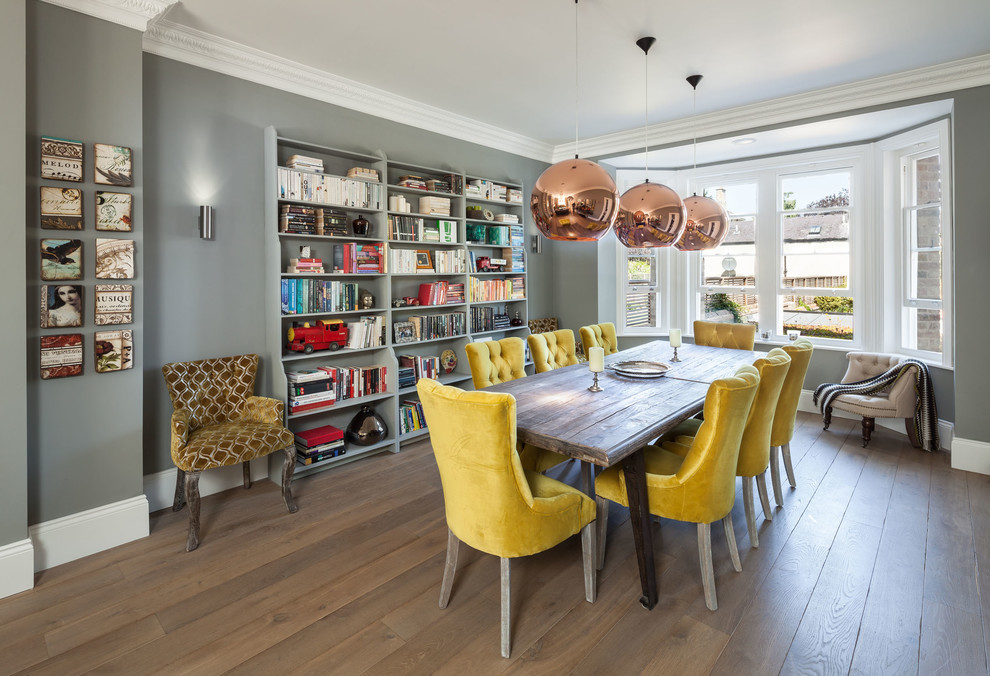 Example of a mid-sized classic medium tone wood floor dining room design in Oxfordshire with gray walls and no fireplace