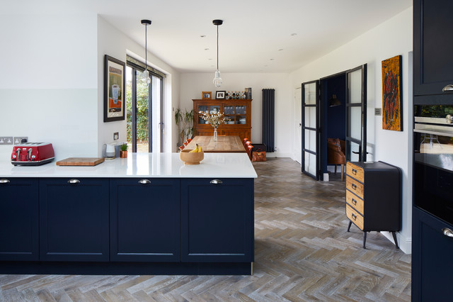 Example of a large minimalist light wood floor and brown floor kitchen/dining room combo design in London with white walls and no fireplace