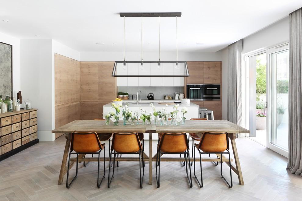 Immagine di una sala da pranzo aperta verso il soggiorno design con pareti bianche, pavimento in legno massello medio, nessun camino e pavimento grigio