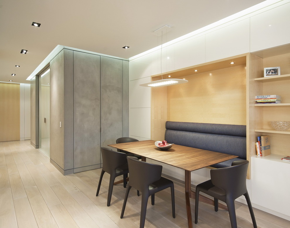 Example of a minimalist light wood floor dining room design in New York with white walls