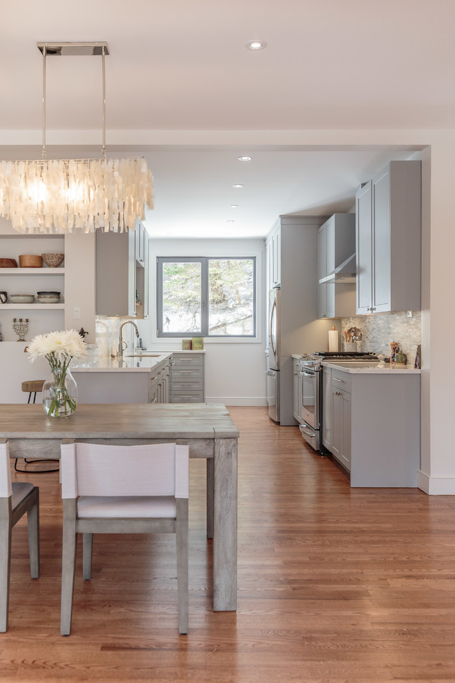 Kitchen/dining room combo - mid-sized transitional medium tone wood floor and brown floor kitchen/dining room combo idea in Montreal with white walls and no fireplace