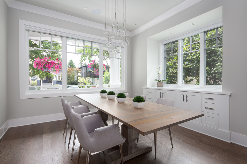Photo of a medium sized classic enclosed dining room in Vancouver with grey walls, medium hardwood flooring, no fireplace and brown floors.