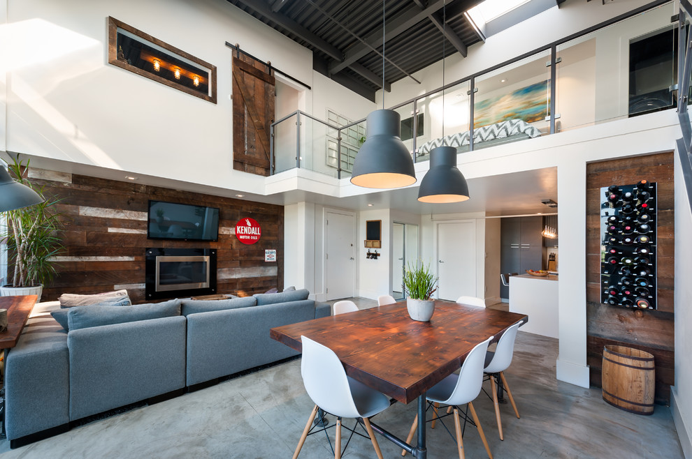 Inspiration for an industrial concrete floor great room remodel in Vancouver with white walls