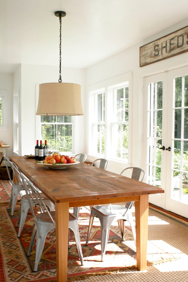 Example of a beach style dining room design in New York with white walls