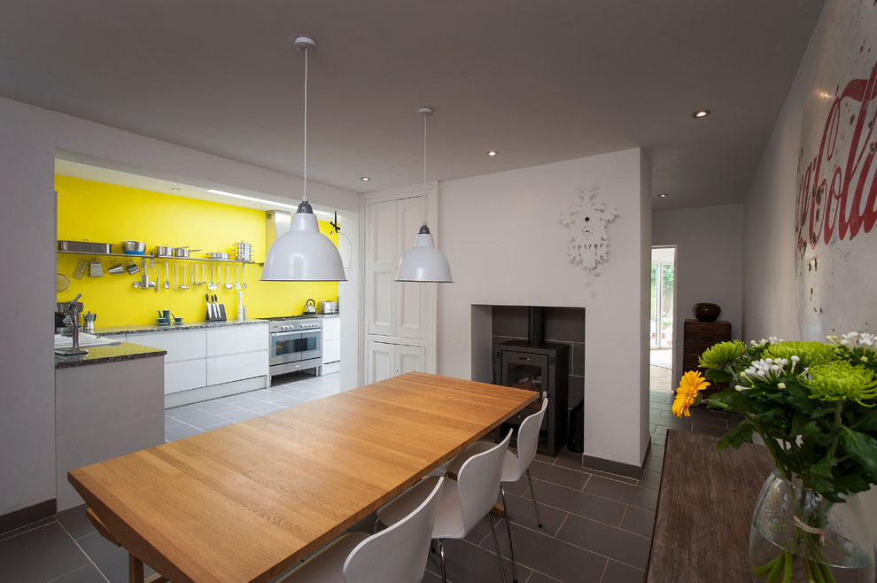 Trendy ceramic floor and gray floor kitchen/dining room combo photo in Gloucestershire with a tile fireplace, white walls and a wood stove