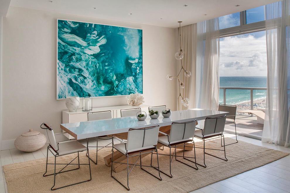 Example of a beach style light wood floor dining room design in Miami with beige walls