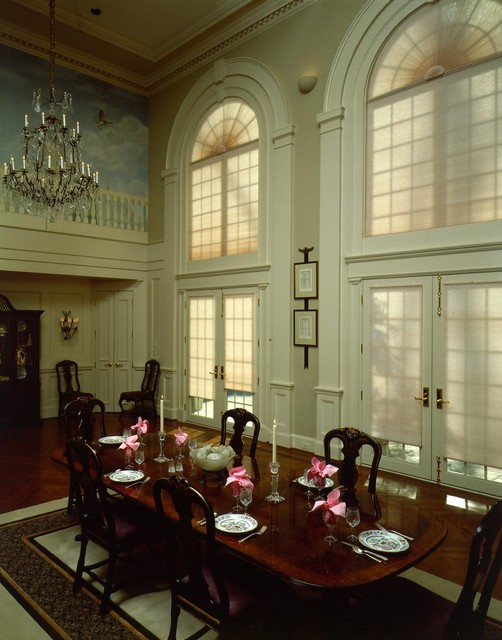 Wall of windows with shades add light privacy to a for Formal dining room window treatments